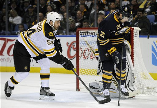 Boston Bruins defenseman Adam McQuaid (54) chases Buffalo Sabres right winger Drew Stafford (21) as he eyes an incoming shot during the first period of an NHL hockey game in Buffalo, N.Y., Wednesday, Oct. 23, 2013. (AP Photo/Gary Wiepert)