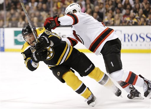 Boston Bruins' Brad Marchand, left, is checked by New Jersey Devils' Marek Zidlicky, of the Czech Republic, during the second period Saturday in Boston.