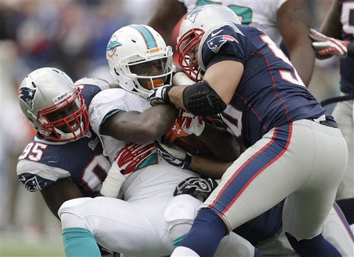 New England Patriots defensive ends Chandler Jones and Rob Ninkovich tackle Miami Dolphins running back Lamar Miller in the third quarter of the Patriots' 27-17 win Sunday at Gillette Stadium in Foxborough, Mass.