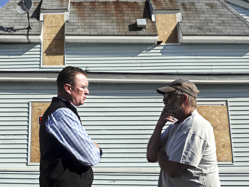 City of Augusta Code Enforcement Officer Rob Overton, left, confers with Weston MacMaster Monday outside the apartment building that MacMaster inhabited at One Jefferson Street. MacMaster was forced to relocate to an apartment in Rumford after the city ordered the Augusta apartment building closed due to safety code violations.