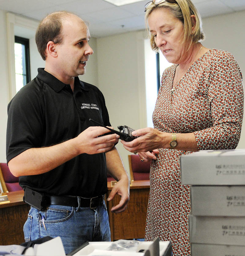Kennebec County Emergency Management Agency planner Art True, left, shows MSAD 11 Superintendent Patricia Hopkins a two-way radio Monday at her Gardiner office. The county EMA procured radios for most schools in Kennebec County to have in case of an emergency. The Gardiner area district is the first to receive the radios, officials said.