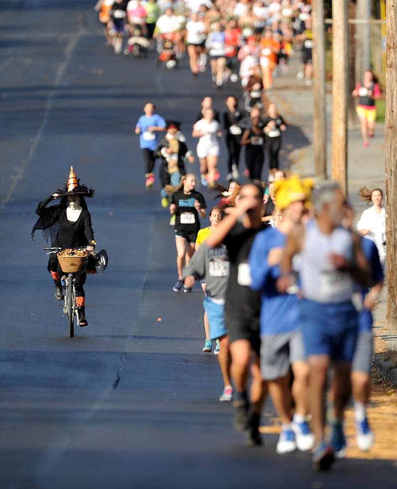Laura Patterson, left, rides her bike dressed as a witch as nearly 200 runners file down Mayflower Hill Road during the Freaky 5K Fun Run that starts and stops at Colby College organized by Hardy Girls Healthy Women today.