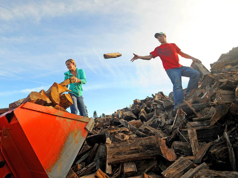 Marissa Hawes, 15, and her boyfriend Brandon Bickford, 17, load the front bucket of their back-ho with firewood at Hawes Logging, Excavation and Firewood in Belgrade on Thursday. The two have been whittling down the pile of wood, which they estimate to be well over 200 cords, since July.