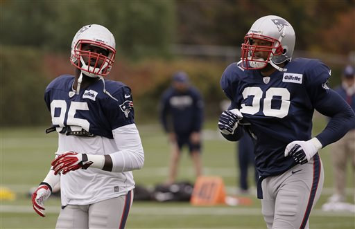 New England Patriots defensive end Chandler Jones (95) and newly reacquired defensive end Andre Carter (96), right, run during a stretching and drills session before practice begins at the NFL football team's facility in Foxborough, Mass., Wednesday, Oct. 23, 2013. The Patriots will play the Miami Dolphins Sunday. (AP Photo/Stephan Savoia)