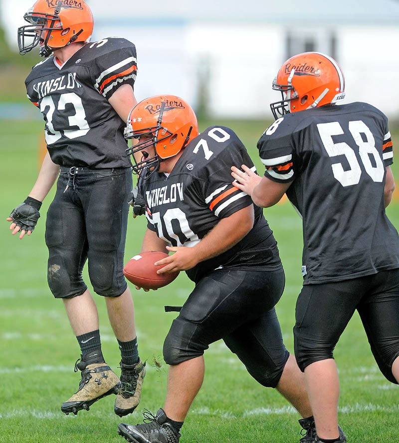 COMING UP BIG: Winslow High School's Aaron Lint, center, celebrates after recovering a fumble earlier this season. Lint is part of a Black Raiders defensive line that has helped Winslow hold its opponents to just 12 points per game this season.
