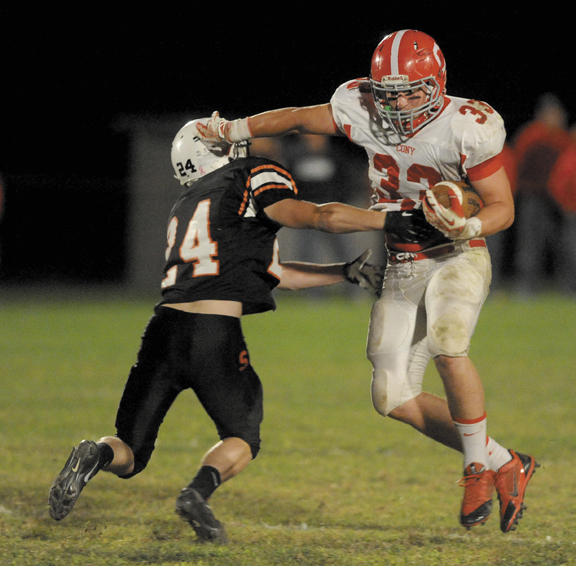 ON THE RUN: Cony running back Reid Shostak, right, stiff arms Skowhegan's Nathan Morris during the Rams' 31-12 win Friday night in Skowhegan.