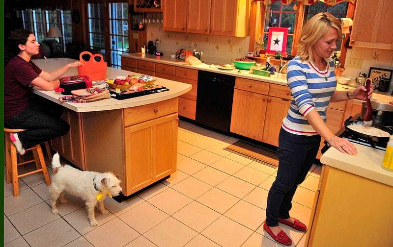 Kimberlee Lewis, left, chats with her mother, Lynn Lewis, while she makes dinner on Wednesday at their home in Monmouth.