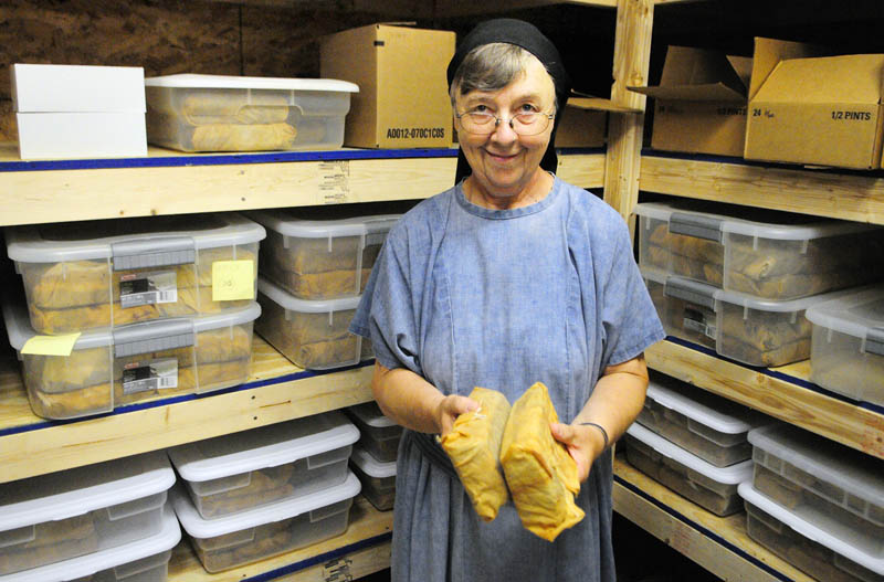 Sister Elizabeth Wagner holds two English Style fruit cakes wrapped in brandy-soaked clothes on Thursday at Transfiguration Hermitage in Windsor. Sister Bernadette Kasinathan bakes the cakes earlier in the year and they're aged in sealed plastic tubs till Wagner decorates and mails them out as orders come in the fall.