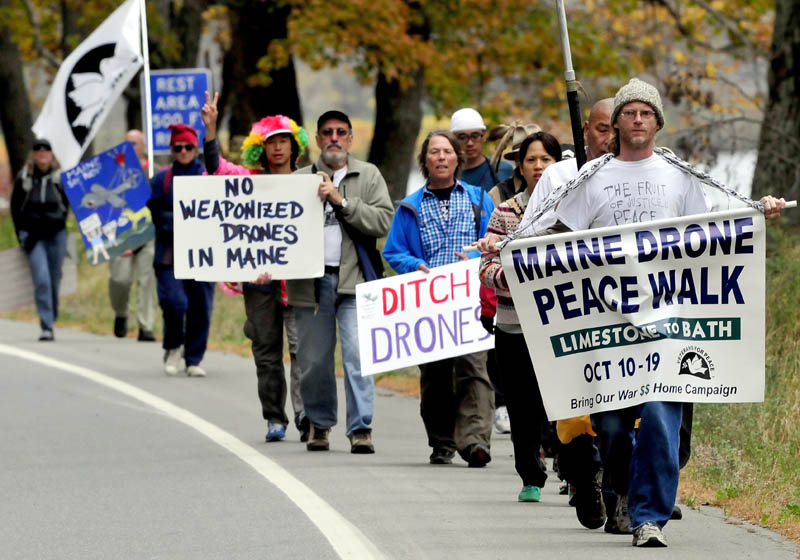 Anti-drone technology marchers led by Jason Rawn, front, make their way through Skowhegan along Route 2 on Sunday. Organizer Bruce Gagnon of Veterans for Peace holds his sign at center.