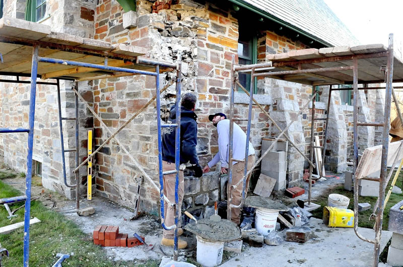 Joseph Lynch, left, and Eric Timmins repair stonework on the outside of the Pine Grove Cemetery chapel in Waterville on Monday. Timmens found a time capsule box near the corner stone of the building that contains four 1907 Morning Sentinel pages and a penny.
