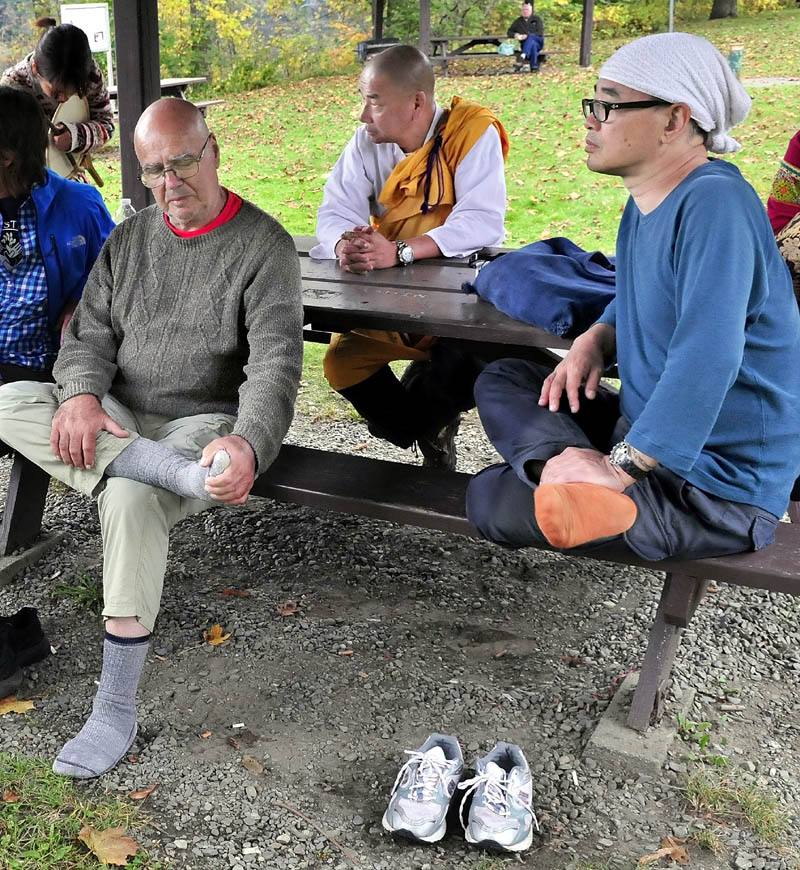 Marchers against the use of drone technology take a break on their march at the rest area along Route 2 in Skowhegan on Sunday. Jules Orkin, left, and Jiro Izuhara took off their shoes to rest their feet. Senji Kanaeda is at center.