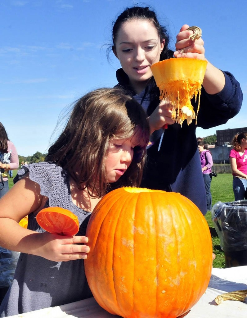 Colby College student Carmen Cordova lifts the top of a pumpkin that she cut as Kate Boudreau peers inside during the Harvest Fest in Waterville on Sunday.