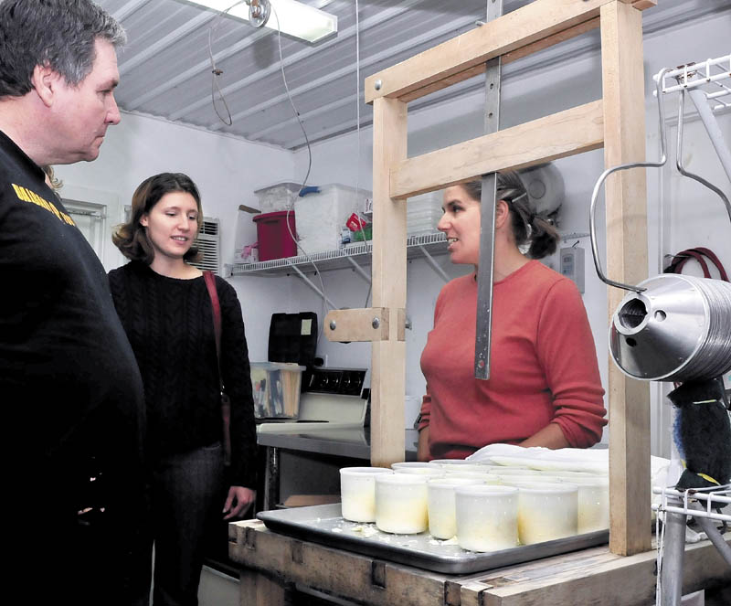 Heather Donahue, right, speaks behind a cheese press about the process of making the cheese at Balfour Farm in Pittsfield during the statewide Open Creamery Day on Sunday. Patrons, including Mike and Emily Boutin, got a chance to see how processors make various cheese products.