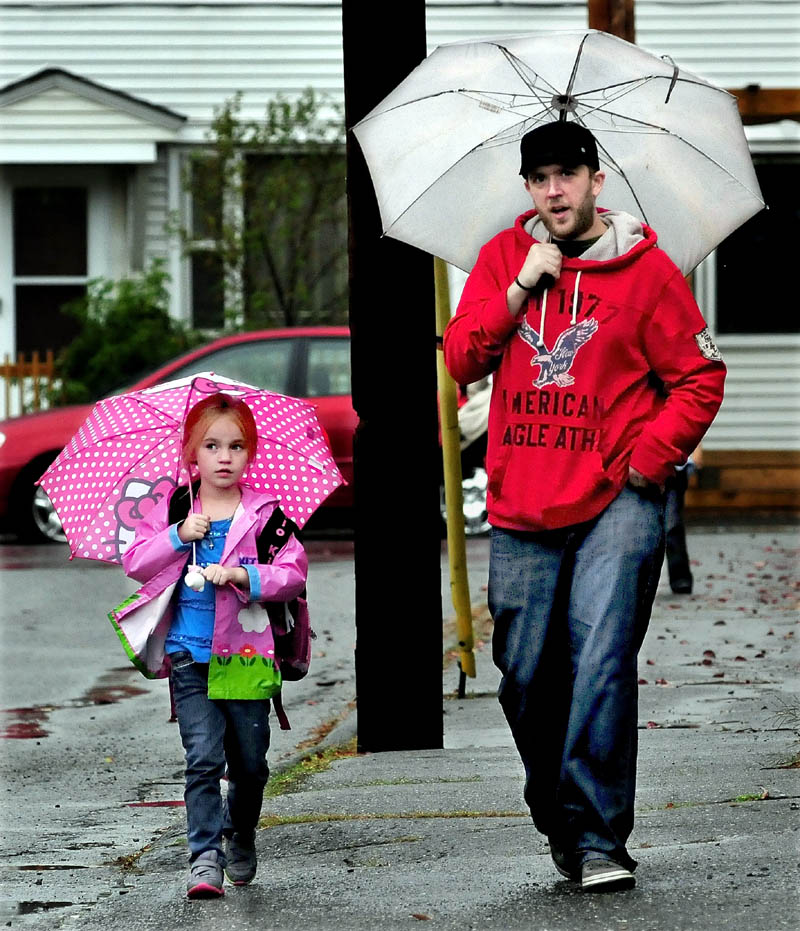 Arthur Caron walks Roslyn Leary home in the rain in Waterville on Monday. The rest of the week is expected to be sunny with moderate temperatures.