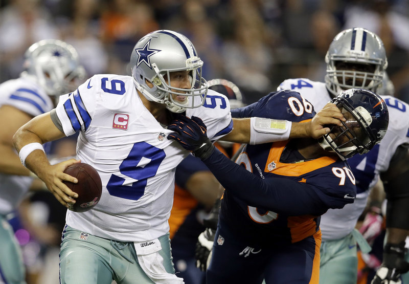 Dallas quarterback Tony Romo, who threw for 506 yards, attempts to fight off a sack by Denver's Shaun Phillips late in the fourth quarter of a high-scoring affair in Arlington, Texas. The Broncos won 51-48.