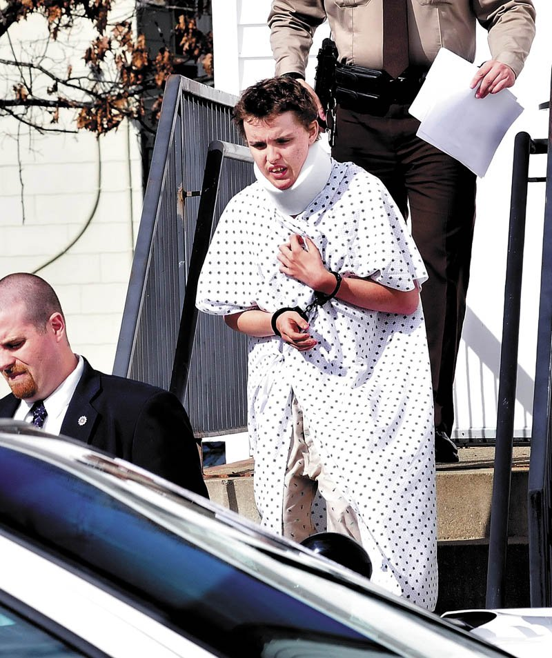 Wearing a hospital gown and neck brace from injuries sustained earlier on Tuesday, suspect Zachary Wittke exits the Franklin County District Court in Farmington following a hearing on charges of eluding police, passing a roadblock and aggravated criminal mischief.