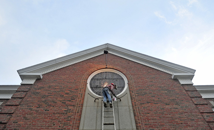 Staff photo by Michael G. Seamans CHURCH WORK: D.L. Allen, a painter with G&L Painting, of Fairfield, continues his work painting the Pleasant Street United Methodist Church on Thursday. The crew has been working on the church for the past week.