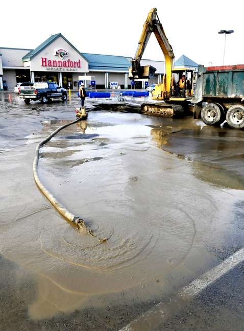 WATER PIPE BREAK: Gerald MacKenzie company workers John Cote, left, and Bob Nickerson work on repairing a water main break in the middle of the Elm Plaza shopping center parking lot in Waterville on Wednesday. Water was unavailable to stores.