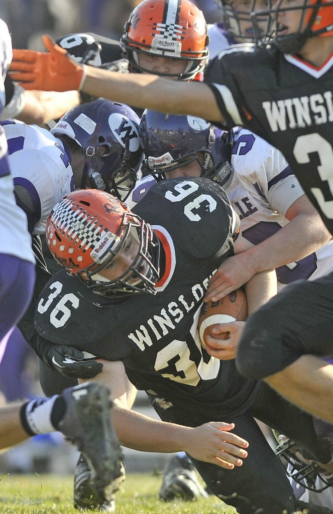 Staff photo by Michael G. Seamans Winslow High School running back Zach Guptill, 36, is tackled by Waterville Senior High School defenders in the second quarter in Winslow on Saturday. Winslow defeated Waterville 49-12.