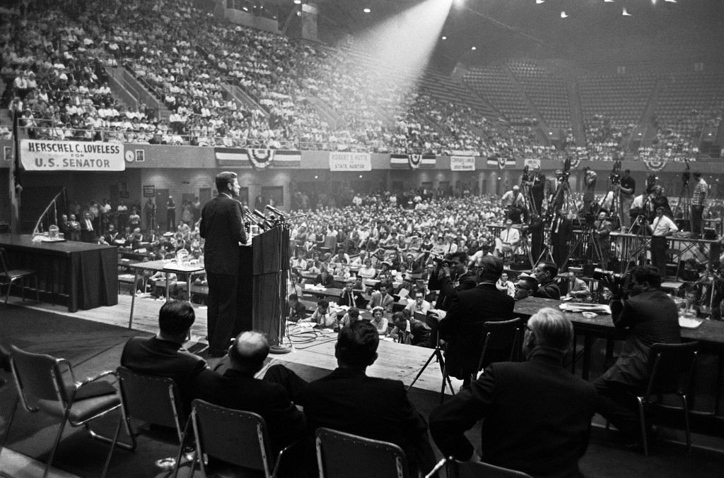 In this Aug. 21, 1960 file photo, illuminated by a spotlight, Sen. John F. Kennedy, Democratic presidential nominee, speaks to an audience in Des Moines, Iowa.