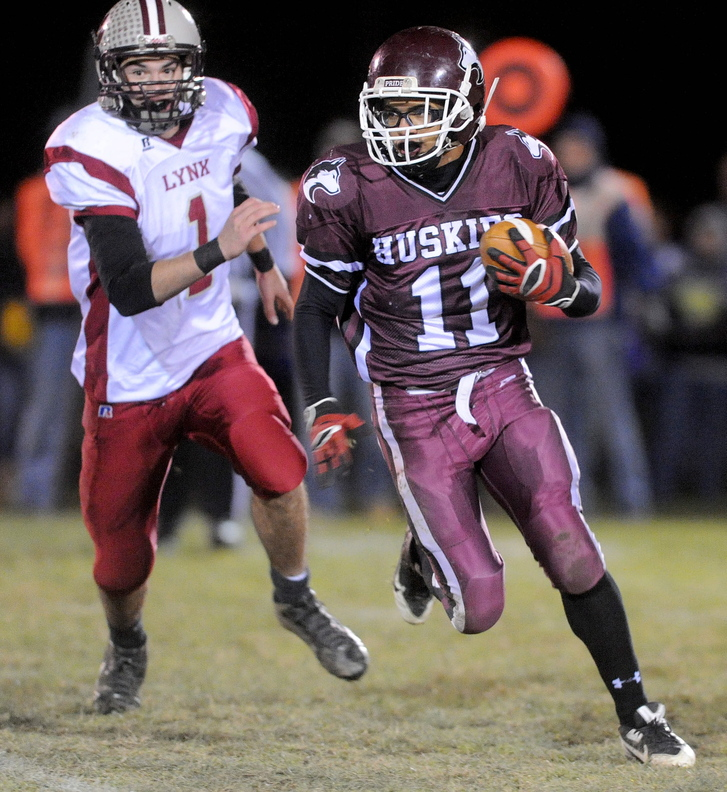 ON THE RUN: Maine Central Institute's Jonathan Santiago, 11, runs as he is pursued by Mattanawcook Academy's Trysten Pelky, 1, in the first quarter in Pittsfield on Friday night.