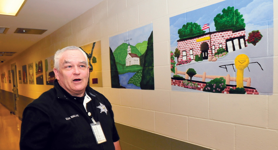ARTFUL: Somerset County Jail officer Sean Maguire explains how 28 Somerset area town landmark paintings will be made into postcards as part of a prison industry project at the Madison facility.