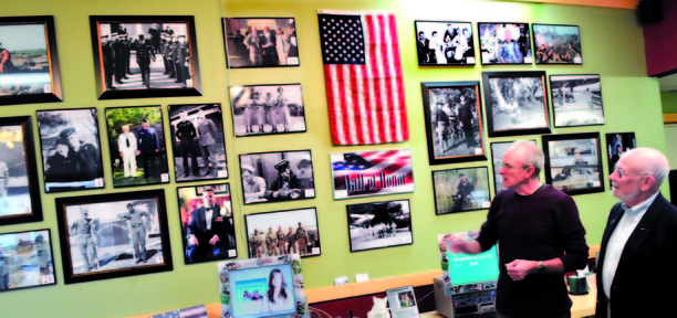 HONOR: Elm City Photo owner John Goodine, left, and Tom Longstaff , both service veterans, look over the two-dozen photographs of area veterans displayed for Veterans Day at the Waterville store on Sunday, Nov. 10, 2013.