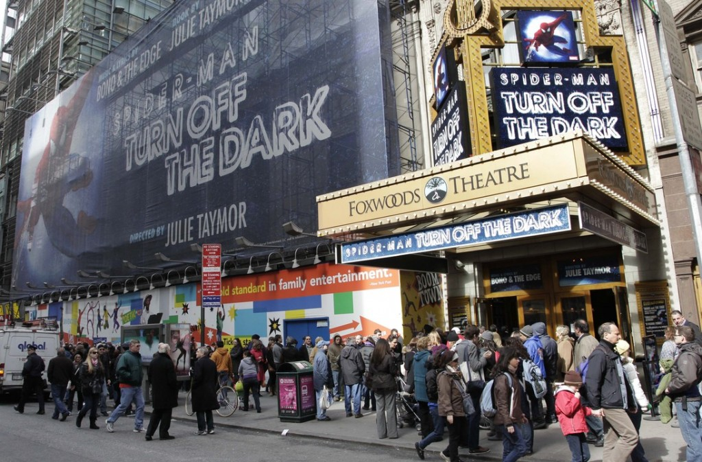 """FILE - In this March 9, 2011, file photo, people line up to enter the Foxwoods Theatre for a matinee showing of """"Spider-Man: Turn Off the Dark,"""" in New York. Producers are turning the lights off forever on the Spider-Man musical on Broadway in early 2014, the final chapter in the story of most expensive theatrical show ever that shook off a troubled launch to become a hit and is now limping away to Las Vegas."""