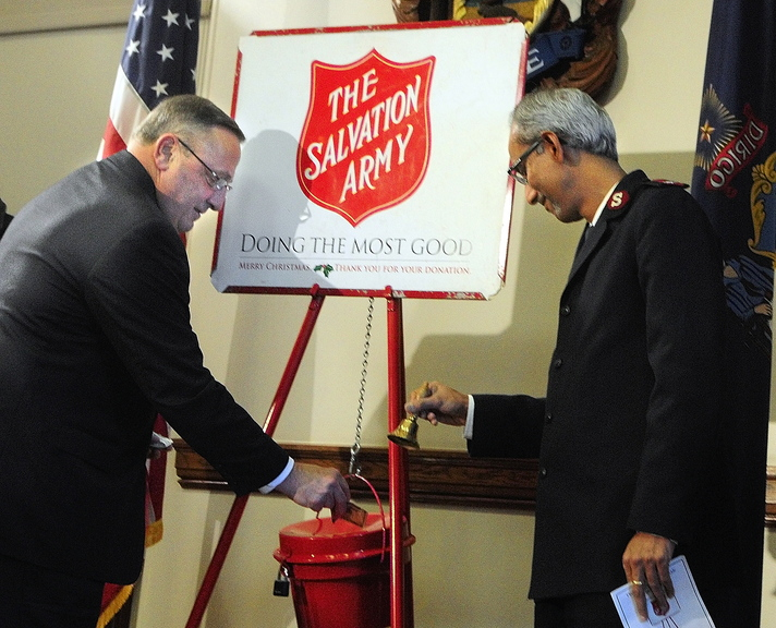 Kettle donation: Gov. Paul LePage, left, slips some cash into a Salvation Army kettle Thursday in the State House Cabinet Room in Augusta as Maj. Asit George, right, rings a bell. He and others from the Salvation Army were there for a statewide kettle kickoff. The Salvation Army has been using kettles annually to collect donations since 1891, according to a Salvation Army news release.