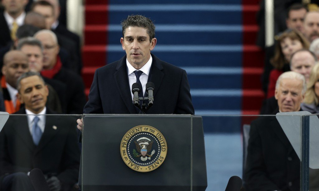 In this Jan. 21, 2013 file photo, poet Richard Blanco speaks at the U.S. Capitol in Washington during the inauguration for President Barack Obama, left, and Vice President Joe Biden right. Blanco describes writing the inaugural poem in his new book, ìFor All of Us, One Today: An Inaugural Poetís Journey.î A Cuban-American who grew up in Miami, Blanco says he was he was forced to re-examine his relationship with his adopted country in the weeks leading up to the inauguration. (AP Photo/Pablo Martinez Monsivais)
