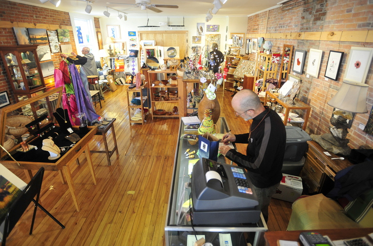 Shopping small: James Albert writes out a receipt for a shopper Saturday at River Roads Artisans Gallery on Water Street in downtown Skowhegan. Small Business Saturday kicked off the weekend following a big Black Friday.