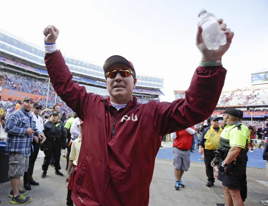 Florida State head coach Jimbo Fisher raises his arm to fans as he comes off the field after defeating Florida 37-7 in Gainesville, Fla., Saturday.