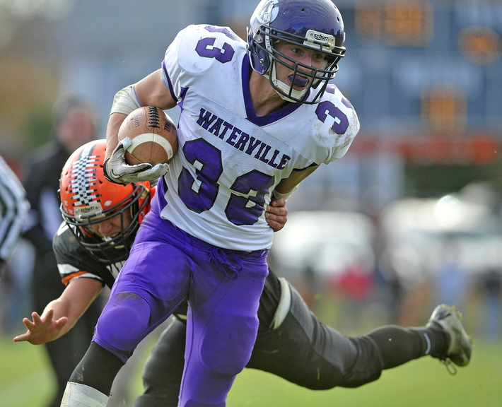Staff photo by Michael G. Seamans Waterville Senior High School's Troy Gurski, 33, breaks a tackle against Winslow High School in Winslow on Saturday. Winslow defeated Waterville 49-12.