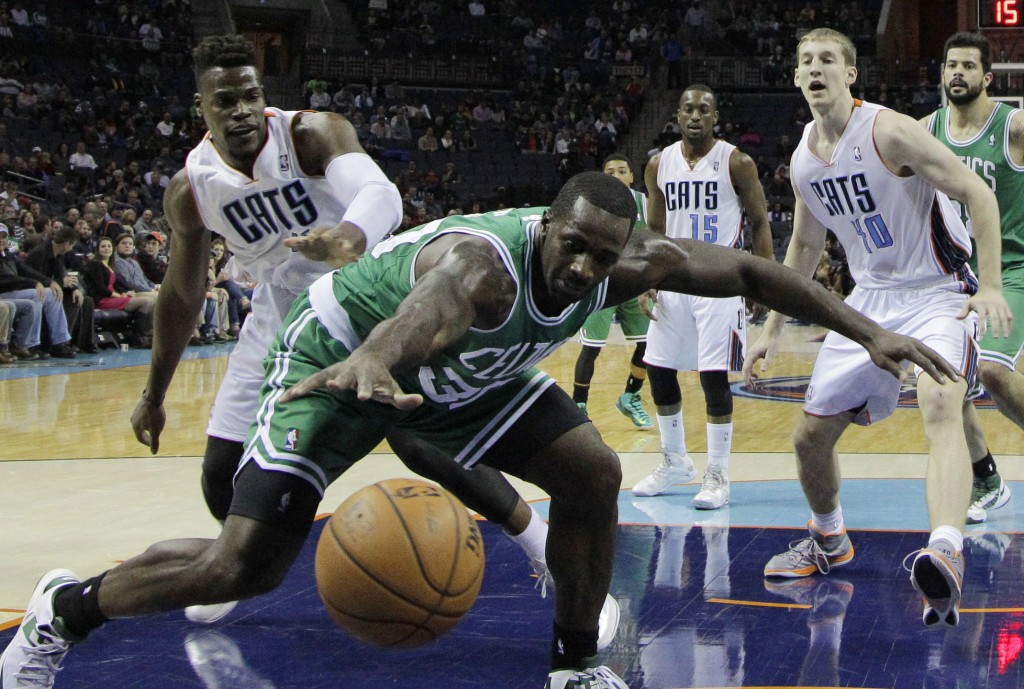 Boston Celtics' Brandon Bass, center, reaches in vain for the ball as Charlotte Bobcats' Jeff Adrien, left, and Charlotte Bobcats center Cody Zeller (40), right, defend during the first half of an NBA basketball game in Charlotte, N.C., Monday, Nov. 25, 2013. (AP Photo/Chuck Burton)