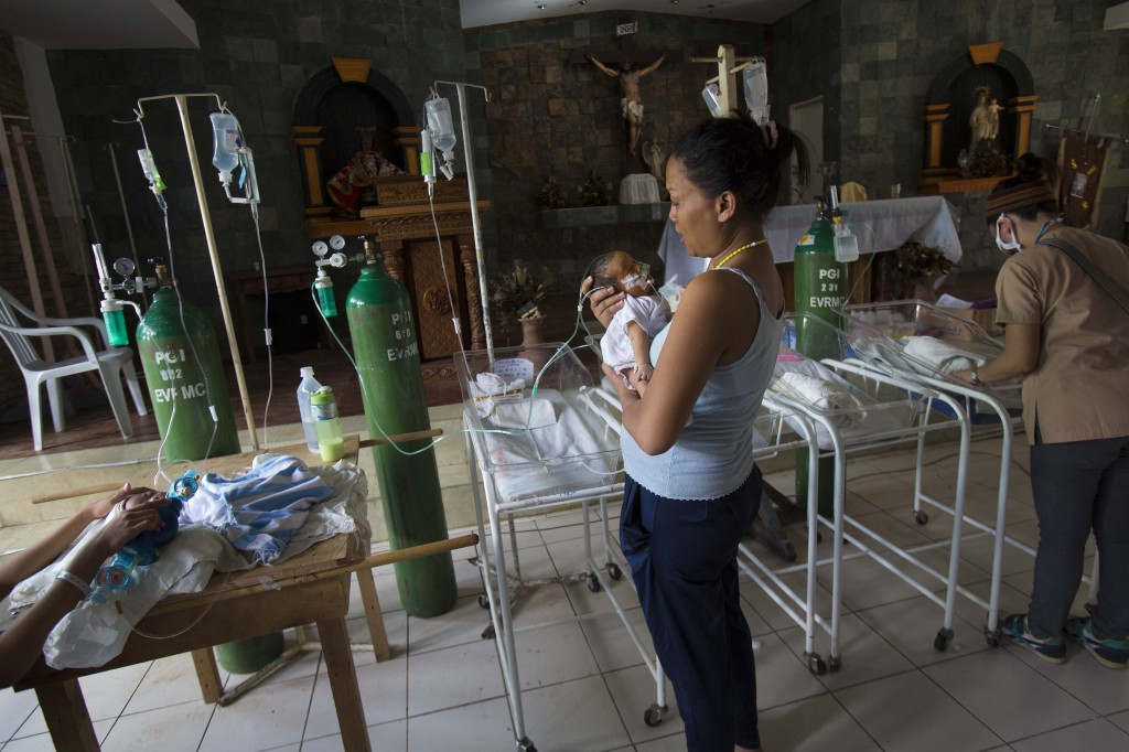 Nanette Salutan holds her baby son, Bernard, in her arms in front of the altar of a Catholic chapel inside the Eastern Visayas Regional Medical Center in Tacloban, Philippines on Saturday. The chapel is now being used to care for infants after Typhoon Haiyan destroyed the original facility of the hospital.