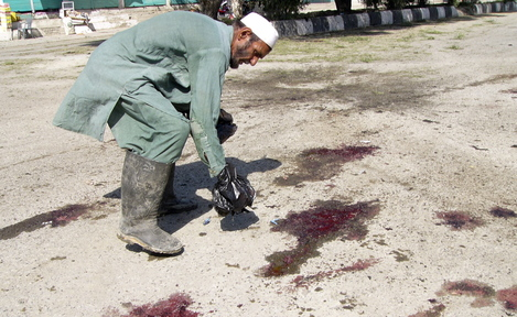 """An Afghan man inspects the scene of a suicide bombing in Khost province in October 2012 that killed three NATO soldiers, an Afghan interpreter and at least nine civilians. The State Department rejects the claims by many interpreters who helped U.S. forces that they face """"serious threats"""" in Afghanistan."""
