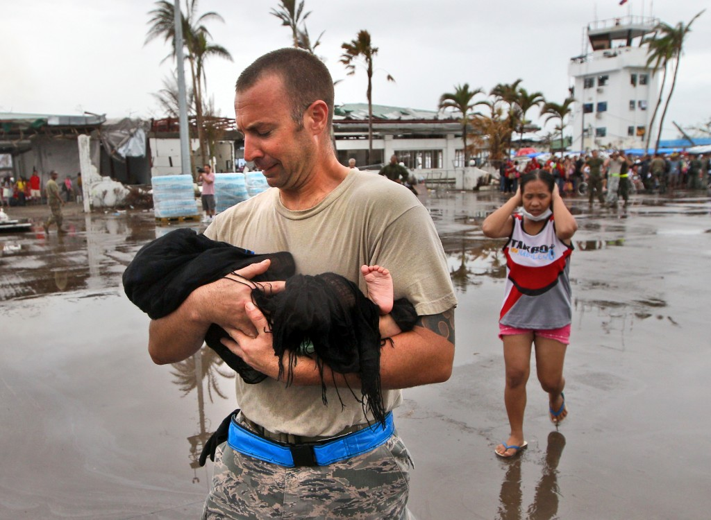 U.S. Air Force Sgt. Jody Dessicino of Egg Harbor, N.J., helps a mother carry her baby to board an evacuation flight at the airport in Tacloban, Philippines, on Friday.