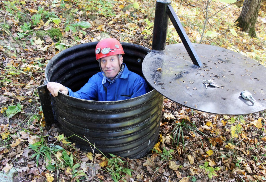 John Ackerman poses in a shaft entrance to his Temple of Doom, one of the 37 caves on his property near Spring Valley, Minn. Associated Press
