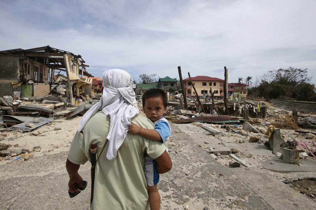 A man walks home with his son Monday, following Friday's devastating typhoon that lashed Hernani township, in eastern Samar province, in the central Philippines.