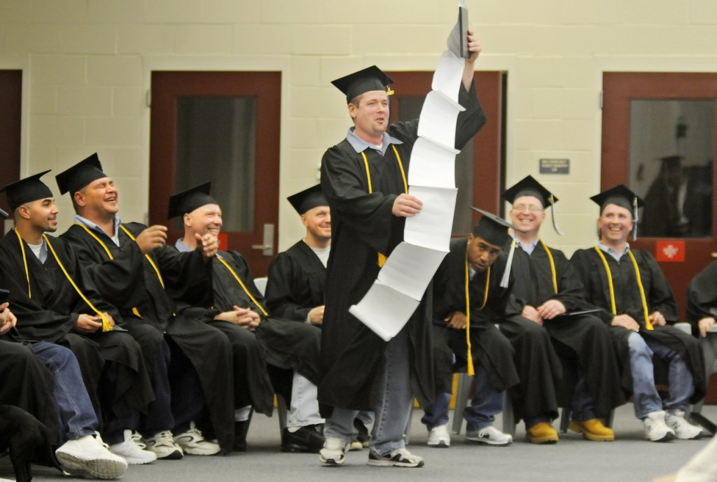 Thankful: Maine State Prison inmate Steven Clark holds up a speech about everyone he wanted to thank Monday after he and 13 other men incarcerated at the Warren prison received their diplomas from the University of Maine at Augusta.