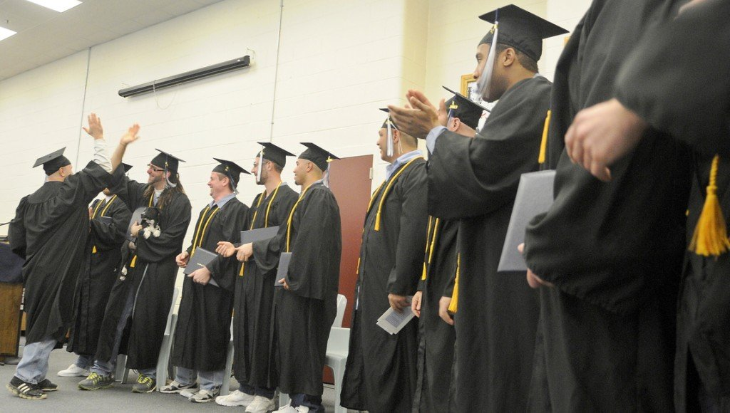 HERE COMES THE GRADs: Maine State Prison inmates congratulate each other Monday after receiving diplomas at the Warren prison from the University of Maine at Augusta.
