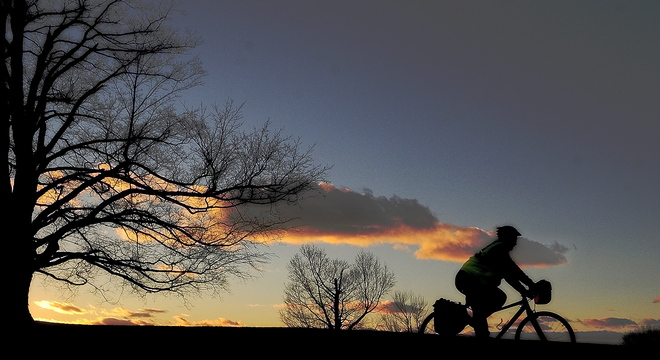 A cyclist rides north as the sun sets behind a tree on Tuesday on Hospital Street in Augusta.