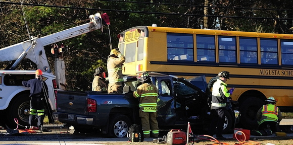 A tow truck driver lifts the bus off a pickup truck: as emergency crews work to free the pickup truck's driver at the scene of a crash involving an Augusta school bus Tuesday on Riverside Drive, just south of Stevens Road, in Augusta.