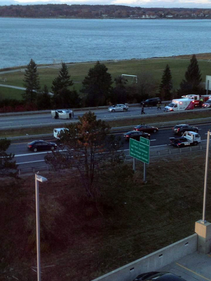 An overturned vehicle lies in the center of Interstate 295 southbound in Portland, trailed by another damaged vehicle and an ambulance.