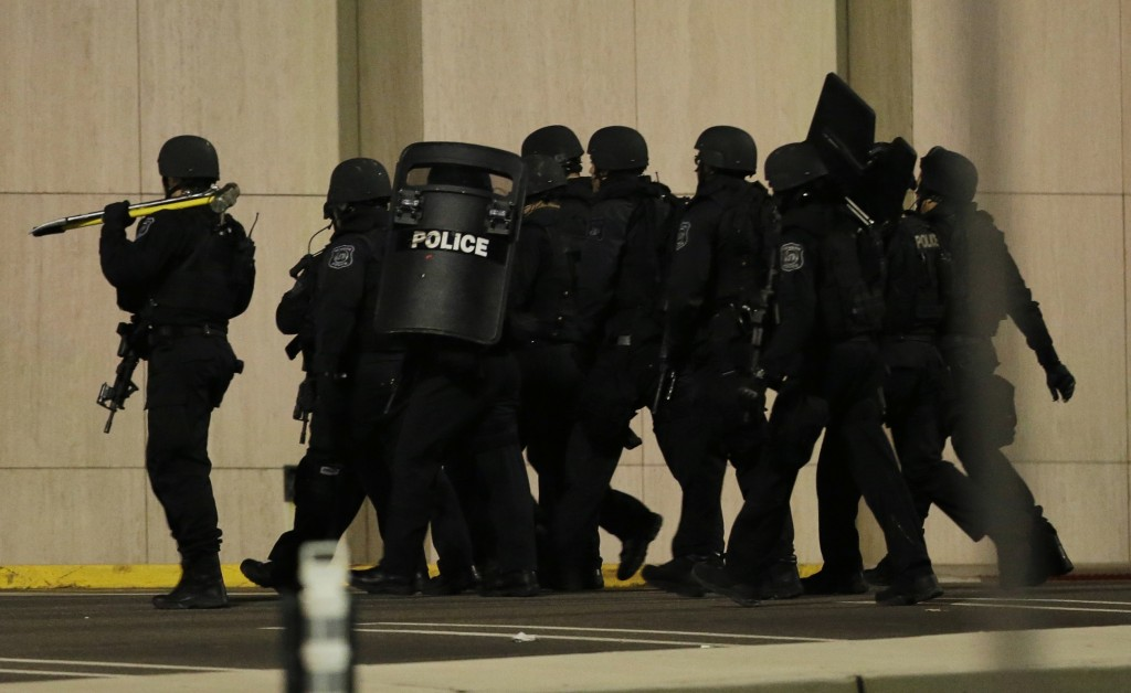 Officials wearing tactical gear walk outside of Garden State Plaza Mall following reports of a shooter in Paramus, N.J. Hundreds of law enforcement officers converged on the mall Monday night after witnesses said multiple shots were fired there.