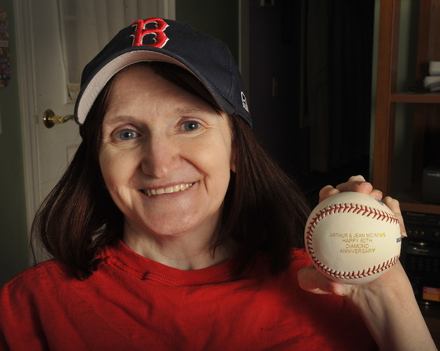 "Kathy McInnis-Misenor of Saco holds a baseball given to her mother and father by the Boston Red Sox on their 60th ""diamond"" wedding anniversary."