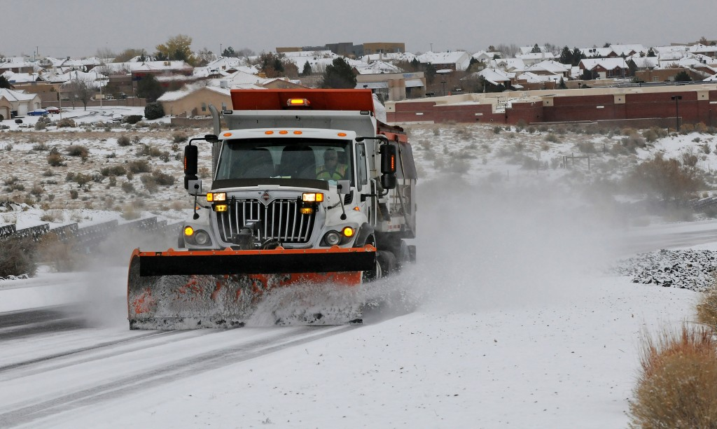 A Deptartment of Transportation plow and sanding truck heads up Paseo del Norte in Albuquerque, N.M., Sunday, Nov.24, 2013, in Albuquerque, N.M., after a winter storm hit New Mexico over the weekend making driving difficult. A large storm already blamed for at least eight deaths in the West slogged through Oklahoma, Texas, New Mexico and other parts of the southwest Sunday as it slowly churned east ahead of Thanksgiving.
