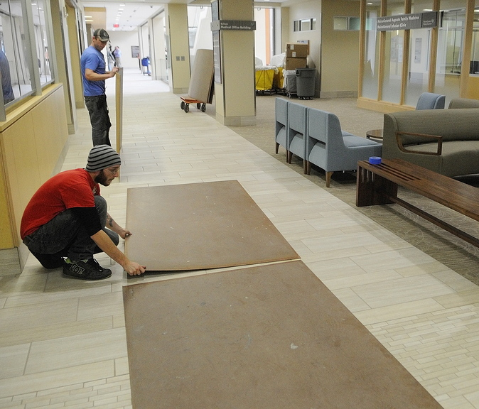 Zachary Curtis, bottom left, and James Ludlow put down boards over the tile in the front hallway on Friday to make it a smoother ride for stretchers that will be rolling through when patients are moved in at the Alfond Center for Health in Augusta.