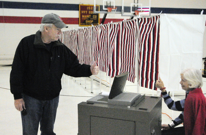 Voter Steve Clarkin, left, and Ward Clerk Louise Lerley exchange thumbs up after the voting machine beeped to show it accepted Clarkin's ballot on Tuesday at the Augusta Ward 1 polling place in the Augusta Armory. The city has new voting machines that will alert a voter if there is a problem with their ballot and give them the option to fix it.