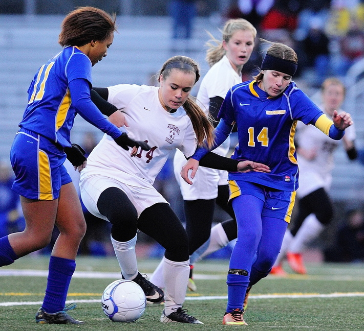 Staff photo by Joe Phelan Richmond forward Amber Loon, middle, is double teamed by Washburn defender Tyra Shaw, left, and midfielder Kennedy Churchill during the state class D soccer championship game on Saturday November 9, 2013 at McMann Field in Bath.
